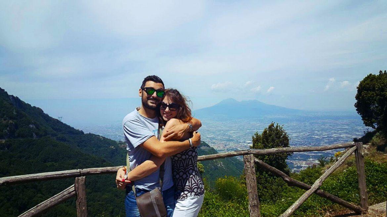 Un ragazzo e una ragazza abbracciati vicino a una staccionata con la montagna e la città alle spalle.