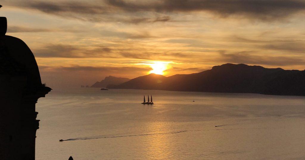 Weekend a Praiano: Vista dal campanile al tramonto con vista sui Faraglioni di Capri e barca a vela a quattro alberi