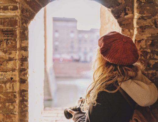 Ragazza bionda con capelli ricci, di spalle con cappello rosso, mentre affacciata ad un arco scatta foto di Ferrara