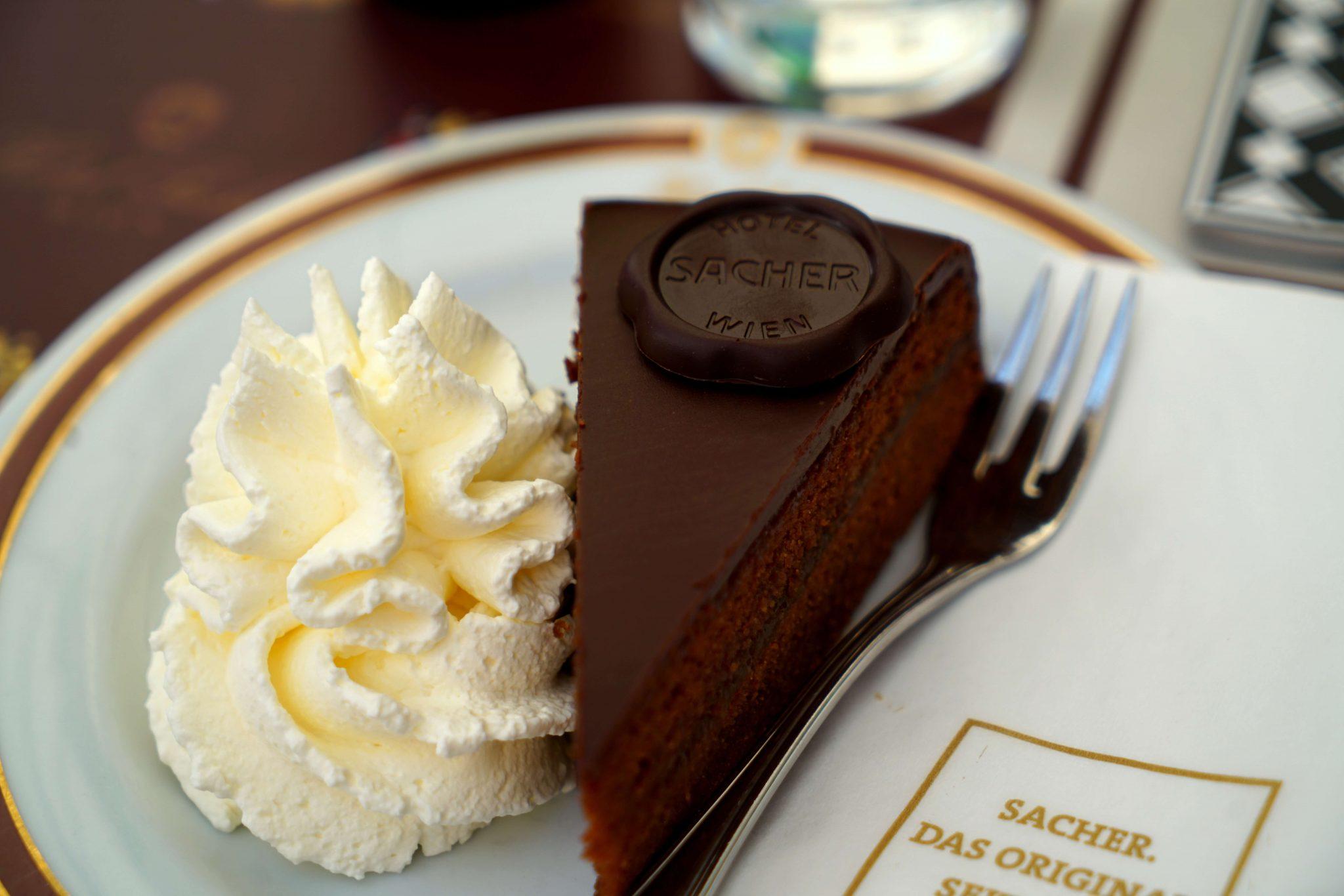 Ricette dal mondo: fetta triangolare di torta al cioccolato con confettura di albicocca e panna montata