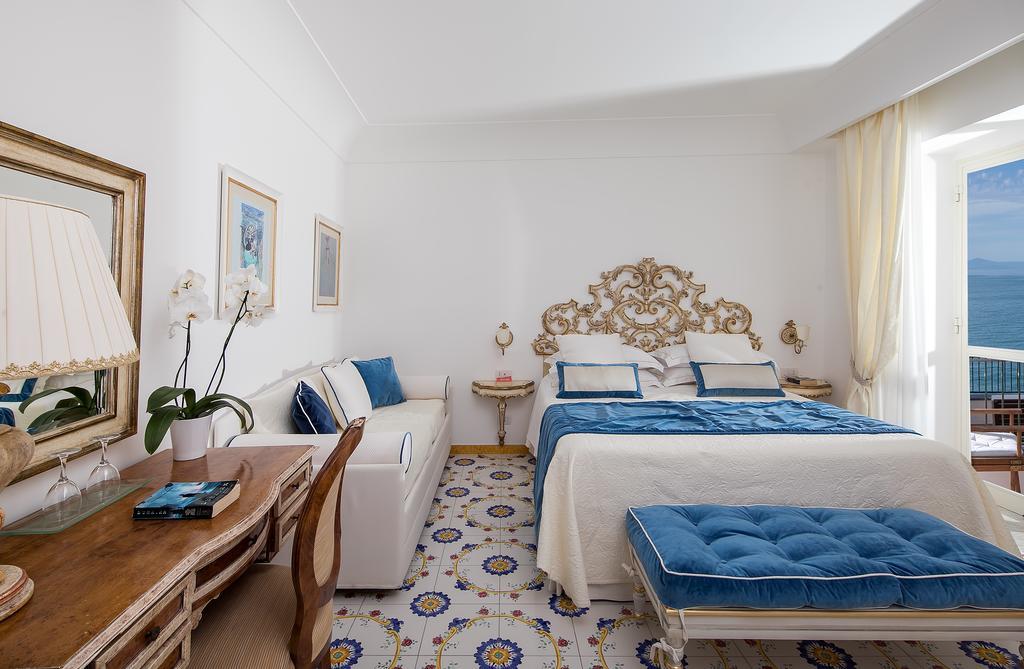 Camera vista mare con maioliche gialle e blu e interni bianchi