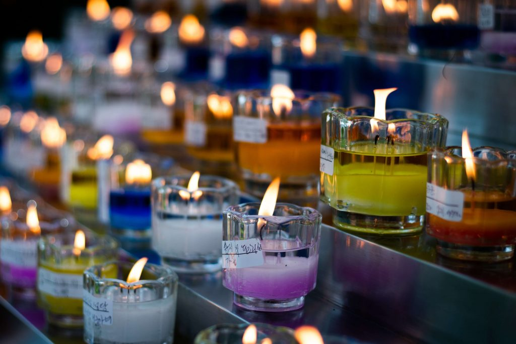 Serie di candele colorate accese in Chiesa in segno di devozione