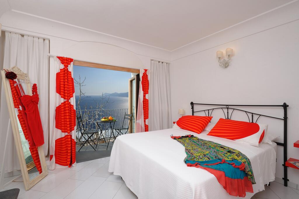 Dormire a Praiano a Casa Erminia: Camera da letto dalle tende bianche e rosse e con balcone con vista su Positano, Capri e Isola dei Galli