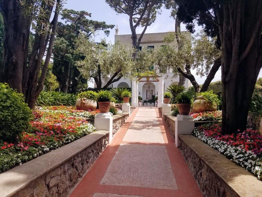 Viale tra fiori colorati rossi, bianchi, rosa e viola su anfore di terracotta.