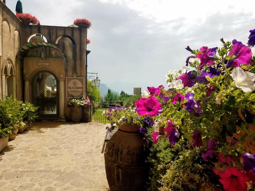 Ingresso Hotel Villa Cimbrone con fiori viola e lilla in primo piano