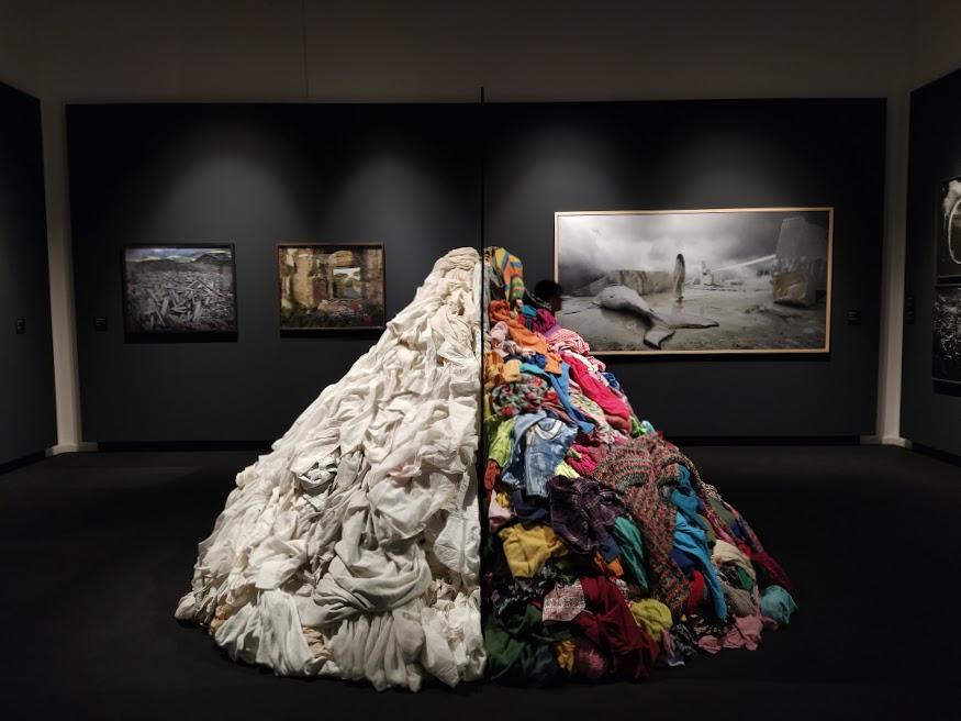 Mostra al PALP di Pontedera: montagna di vestiti per metà bianchi e metà colorati divisi da uno specchio al centro.