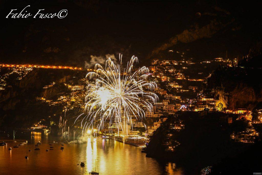 Fuochi d'artificio colorati davanti a Positano tutta illuminata di sera