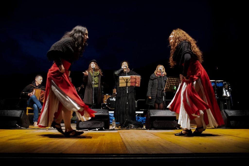 Esibizione dal vivo dell'Orchestra Popolare del Saltarello abruzzese con le cantanti sul retro e due danzatrici di saltarello vestite di rosso in primo piano